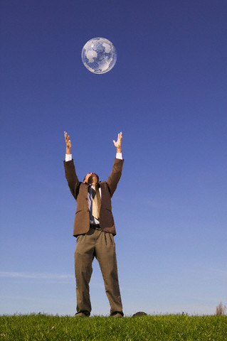 Businessman Tossing Globe into Sky