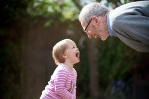Side profile of Grandfather bending down laughing with his Granddaughter in a garden.