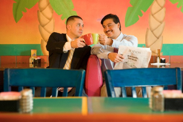 Businessmen clinking coffee cups in a restaurant